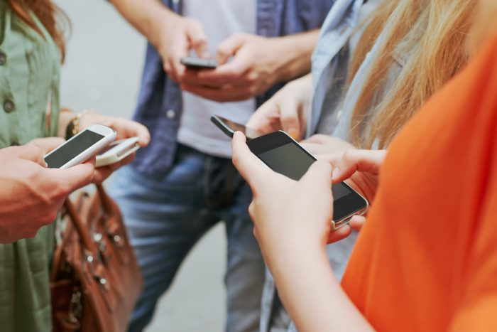 Group-of-friends-all-using-smart-phones